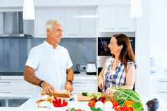 Mature couple cooking at home. Happy couple cooking together at home royalty free stock photo