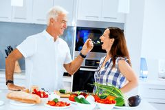 Mature couple cooking at home. Happy couple cooking together at home royalty free stock images