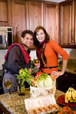 Mature couple cooking in kitchen drinking wine Royalty Free Stock Photos