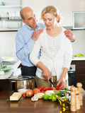 Mature couple cooking together in  kitchen Stock Image