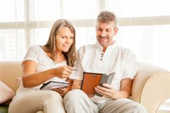 Mature couple on a couch with tablet royalty free stock photo