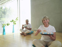 Mature couple on cushions, woman eating sushi with chopsticks, smiling, portrait. Mature couple on cushions, women eating sushi with chopsticks, smiling Stock Image
