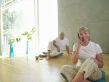 Mature couple on cushions, woman on telephone, smiling, portrait Stock Photo
