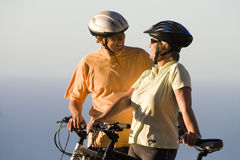 Mature couple, in cycling helmets, standing on clifftop with mountain bikes, Atlantic Ocean in background Stock Photo