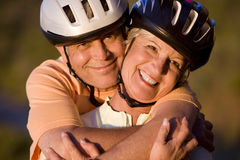 Mature couple, in cycling helmets, standing on mountain trail, man embracing woman, smiling, close-up, portrait Stock Photos