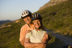 Mature couple, in cycling helmets, standing on mountain trail, man embracing woman, smiling, portrait Stock Photography