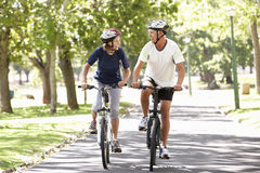 Mature Couple Cycling Through Park Stock Image