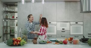 Mature couple dacing charismatic in the kitchen while preparing the healthy breakfast in a modern kitchen design. stock footage