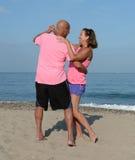 Mature couple dancing on beach Stock Photos