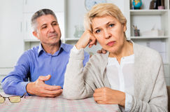 Mature couple decide family matters and find out relationship. Ordinary unhappy mature couple decide family matters and find out relationship in his house Stock Photos