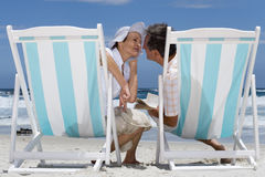 Mature couple on deck chairs on beach preparing to kiss, rear view Royalty Free Stock Photos