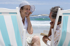 Mature couple on deck chairs on beach sharing earphones, smiling at each other Royalty Free Stock Photography