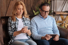 Mature couple demonstrating Internet addiction at home. Concept of Internet addiction. Addicted mature concentrated couple sitting on the couch and using mobiles Stock Photos