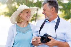 Mature couple with digital camera. Loving Senior Couple Outdoors Smiling Royalty Free Stock Image