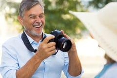 Mature couple with digital camera. Loving Senior Couple Outdoors Smiling Stock Photos