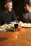 Mature Couple Dining. Out. Shallow dof with focus on wine glass. Couple and background blurred Stock Photos
