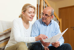Mature couple with documents at home Stock Image