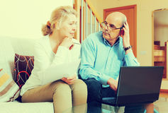 Mature couple with documents and laptop Stock Photos