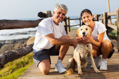 Mature couple dog. Sporty mature couple and pet dog at the beach in the morning Stock Image