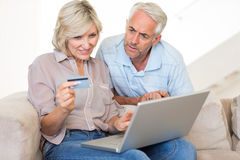 Mature couple doing online shopping at home Stock Image