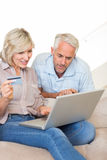 Mature couple doing online shopping at home Royalty Free Stock Photography