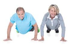 Mature couple doing push-ups Stock Image