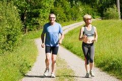 Mature couple doing sport - jogging. Mature or senior couple doing sport outdoors, jogging stock photo