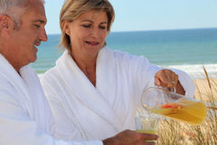 Mature couple drinking on beach Stock Photography