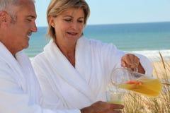 Mature couple drinking on beach Stock Photography