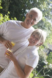 Mature couple drinking orange juice together outdoors Royalty Free Stock Photography