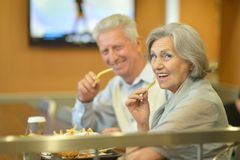 Mature couple eating french fries Royalty Free Stock Images