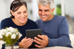 Mature couple emails. Mature couple reading emails on tablet computer Royalty Free Stock Image