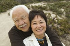 Mature couple embracing at beach smiling (portrait) Royalty Free Stock Photography