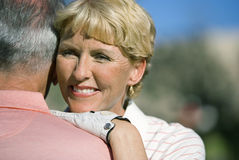 Mature couple embracing on golf course, focus on woman wearing golf glove, smiling, close-up, view over shoulder Royalty Free Stock Photography