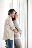 Mature couple embracing at home by a window Royalty Free Stock Photos