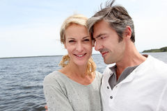 Mature couple embracing by the lake Stock Photos