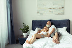 Mature couple embracing and relaxing on bed at home Stock Images