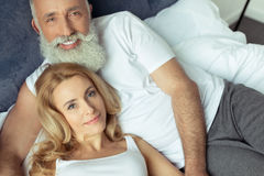 Mature couple embracing and relaxing on bed at home Stock Image