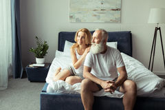 Mature couple embracing and relaxing on bed at home Royalty Free Stock Image