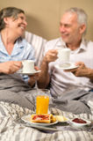 Mature couple enjoying breakfast at hotel room Royalty Free Stock Photo