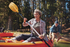 Mature couple enjoying a day at the lake with kayaking. Portrait of happy senior paddling kayak in the lake with men supporting from behind. Mature couple Royalty Free Stock Photo