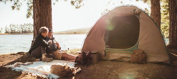 Mature couple enjoying a glass of wine at their campsite royalty free stock images