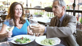 Mature Couple Enjoying Meal At Outdoor Restaurant. As man proposes toast with nice wine.Shot on Sony FS700 in PAL format at a frame rate of 25fps stock video footage