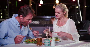 Mature Couple Enjoying Meal At Rooftop Restaurant. Mature couple enjoying meal at outdoor restaurant together.Shot in 4k on Sony FS700 at frame rate of 25fps stock video footage