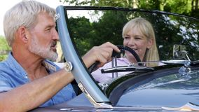 Mature couple enjoying road trip in classic open top sports car together. Mature couple enjoying road trip in classic open top sports car stock video footage