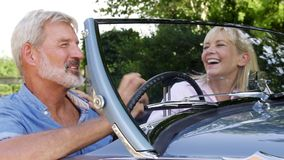 Mature couple enjoying road trip in classic open top sports car together. Mature couple enjoy road trip in classic open top sports car together stock footage