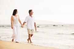 Mature Couple Enjoying Sunset on the Beach. Mature Retired Couple Enjoying Sunset Walk on the Beach Stock Photography