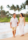 Mature Couple Enjoying Walk on the Beach Stock Photo