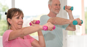Senior couple exercising with dumbbells. Mature couple exercising with dumbbells Royalty Free Stock Photography