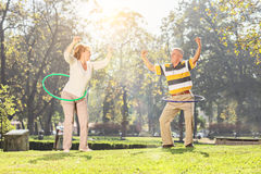 Mature couple exercising with hula hoops in park Royalty Free Stock Photo
